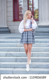 Beautiful girl walking down the stairs talking on the phone. Blonde in white blouse and plaid skirt talking on the phone on the stairs of the building with columns