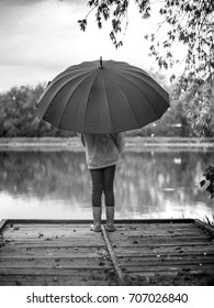 a beautiful girl is walking in the old wooden bridge at sunset after the rain with big black umbrella, black and white