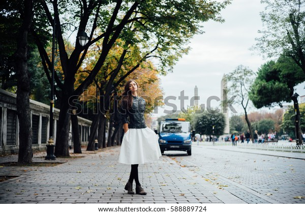 Beautiful girl walking on the cobblestone square. ancient area autumn.car background Soft focus and slight noise of the atmosphere for lifestyle.