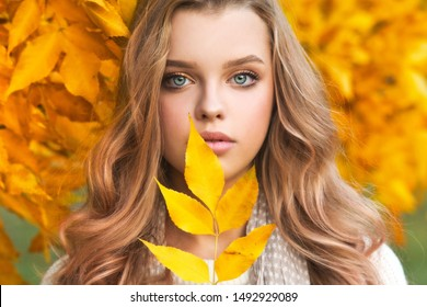 Beautiful girl walking outdoors in autumn. Smiling girl collects yellow leaves in autumn. Young woman enjoying autumn weather.