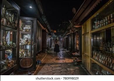 Beautiful girl walking through passage in dark summer night