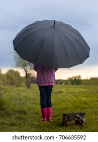 a beautiful girl is walking through a yellow and green field at sunset after the rain with big black umbrella