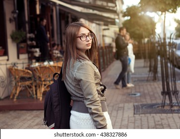 Beautiful girl walks down the street of European city
