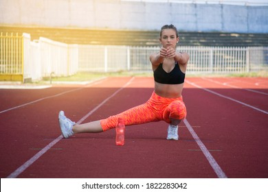 Beautiful girl warms up on the athletic track