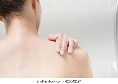 Beautiful girl washing her body shower gel