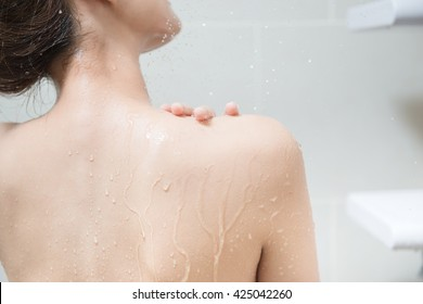 Beautiful girl washing her body shower gel