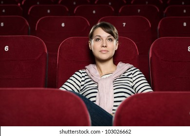 Beautiful girl watching a movie at the cinema