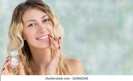 Beautiful girl with wavy hair cares of her lips. Young blonde woman applying make-up cosmetic SPA product lip balm or gloss for hydration, smoothing and skin rejuvenation. Makeup, wellness or skincare