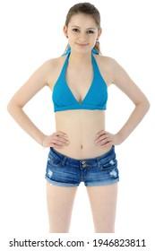 Beautiful girl wearing a blue bikini top and hot pants in studio isolated on white