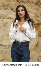 Beautiful girl wearing blue jeans, a white blouse unfastens her blouse in a sandy quarry against the backdrop of a sand wall. Healthy clean skin. Commercial, fashionable and advertising photo