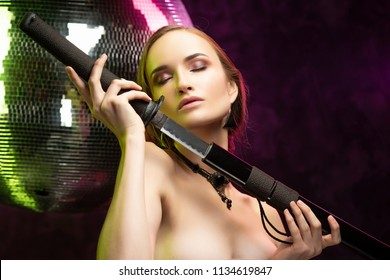 Beautiful girl wearing an elegant necklace and earrings of black opal holds Japanese katana sword in her hands at a mirror disco ball, illuminated by green and pink lights. Healthy skin.