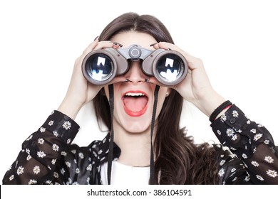 Beautiful girl wearing a floreal shirt and looking through binoculars with surprised expression