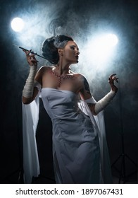 Beautiful girl wearing a Halloween costume with rich make-up and an imitation of an autopsy seam on her chest is emotionally posing holding a cigarette holder in the smoke. Vintage, cosplay design.