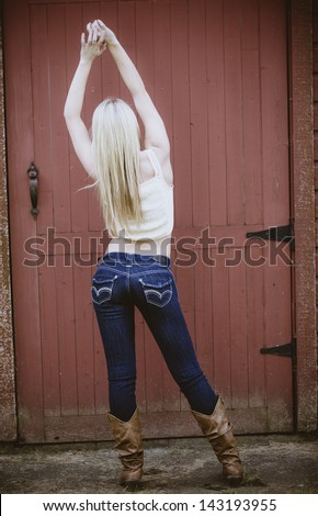 c4999f58423 Beautiful girl wearing jeans and white t-shirt posing with her arms up