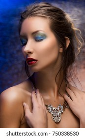 The beautiful girl wearing a necklace on a colourful foil background. Stylized as evening light. Evening colourfull make-up. Red lips. Clean healthy skin.