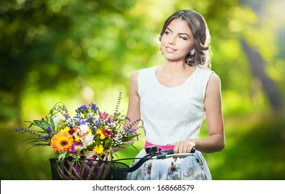 Beautiful girl wearing a nice white dress having fun in park with bicycle carrying a beautiful basket full of flowers. Vintage scenery. Pretty blonde girl with retro look, bike and basket with flowers