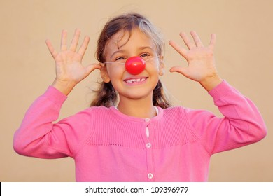 Beautiful girl wearing pink blouse with red clown nose smiles and teases.