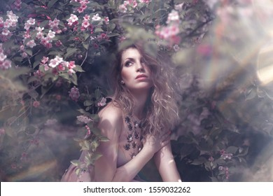 Beautiful Girl wearing a Pink Dress enjoying the Spring Days in a Garden full of Roses in Florence Italy