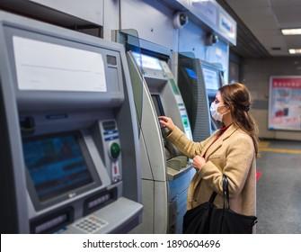 Schönes Mädchen mit Schutzmaske und modische Kleidung verwendet Geldautomat.Neues normales Konzept während pandemischer Korona,covid19.