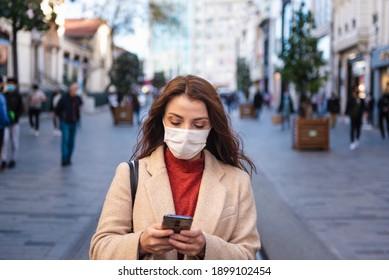 Schönes Mädchen mit Schutzmaske und modischer Kleidung benutzt Smartphone auf der Straße. Neues normales Lifestyle-Konzept.