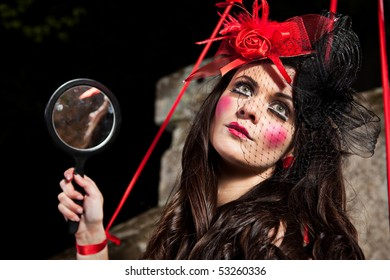 Beautiful girl wearing red hat and striped dress posing as a marionette (puppet on a string)
