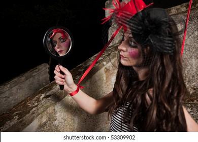 Beautiful girl wearing red hat and striped skirt posing as a marionette (puppet on a string)