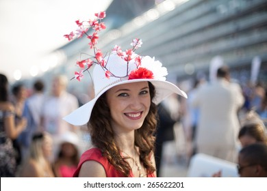 Beautiful girl wearing Sakura flower hat smiling at the Dubai World Cup Horse Race
