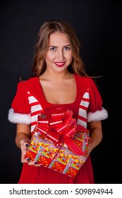 Beautiful girl wearing santa claus clothes with christmas gift