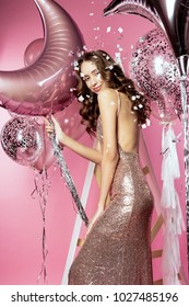 Beautiful girl wearing sparkling tight evening dress posing with helium balloons, gifts, confetti on a pink background. Party, holidays, new year, christmas. Advertising, fashion and commercial Design