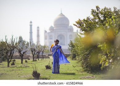 Beautiful Girl wearing traditional Indian Saree posing in a garden in front of Taj Mahal in Agra, India