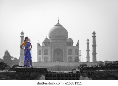 Beautiful girl wearing traditional Indian Saree posing in front of the Taj Mahal in Agra, India