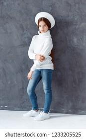 A beautiful girl wearing a white beret. A girl in a studio