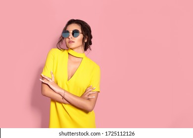 Beautiful girl wearing yellow dress and sunglasses posing on pink background in studio. Looking at camera.