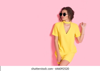 Beautiful girl wearing yellow dress and sunglasses posing on pink background in studio. Looking sideways, copy space.