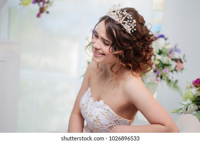 Beautiful girl in wedding dress sitting and smiling. Bride in luxurious dress, close-up