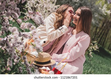 Beautiful girl whispering on ear of her best friends some rumors while sitting outdoors. Young women friends gossiping and laughing while having picnic at blossom park. Women's gossips and rumors