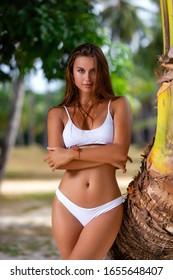 Beautiful girl in white bikini posing near palm tree at the tropical beach