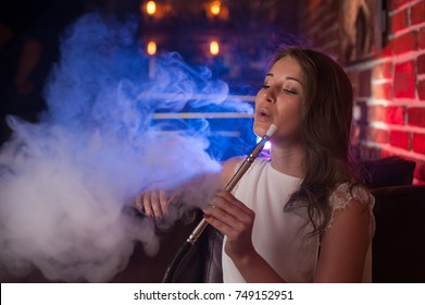 Beautiful girl in a white blouse smokes a hookah in the interior of the bar