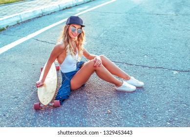 A beautiful girl in a white body bathing suit sits in the summer with longboard skate. Posing against background of road. Happy smiles. In sunglasses and a baseball cap. Long legs and tanned skin.