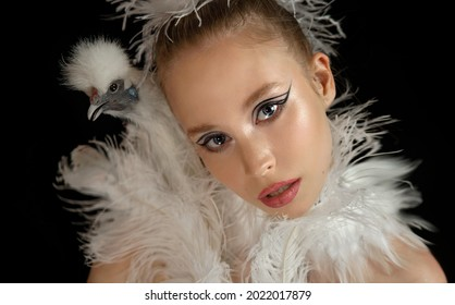 Beautiful girl with a white chicken. Chicken and model. Glamorous chicken. Fashionable makeup.