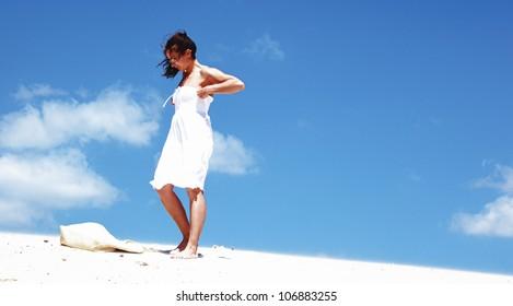 Beautiful girl in white dress with beach bag