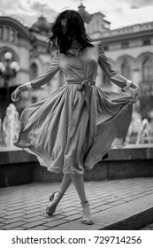 Beautiful girl in a white dress in black polka dots, with a red bow, with curly black hair, walking of the old city. Woman in a dress with a red bow. Retro, fashion. Black and white photo