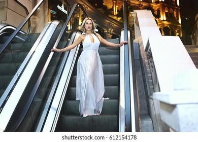 Beautiful girl in a white dress coming down the escalator