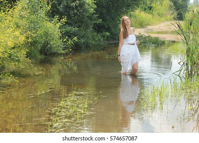 Beautiful girl in white dress enjoying the summer sun outdoors in the park