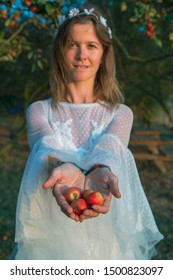 Beautiful girl with white dress in field without makeup holding apple in her hands
