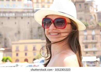 Beautiful girl with white dress and hat, red sunglasses standing in Sorrento Port, in background is a boat, blue sea and sky. Italy