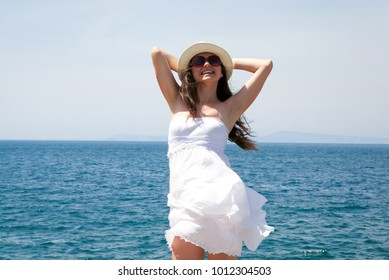 Beautiful girl with white dress and hat, in background is the blue sea and sky. Sorrento, Italy