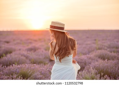 beautiful girl in a white dress and hat in a lavender field at sunset