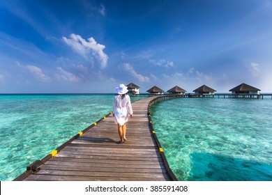Beautiful girl in white dress and hat standing on wooden planks in the Maldives island on the background of a bungalow on the water and the beauty of the sea with the coral reefs