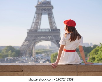A beautiful girl in a white dress, a red beret sits against the backdrop of the Eiffel Tower in Paris. Travel to Paris. Ideas for a photo shoot.